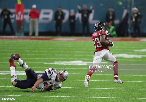 Tom Brady of the New England Patriots attempts to tackle Robert Alford of the Atlanta Falcons after an interception in the second quarter during...