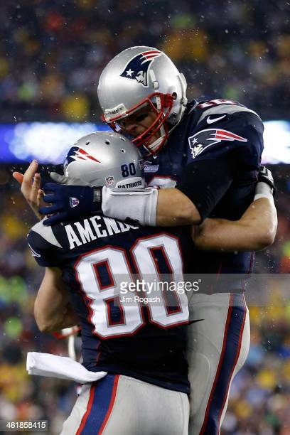 Tom Brady of the New England Patriots celebrates with teammate Danny Amendola against the Indianapolis Colts in the first quarter during the AFC...