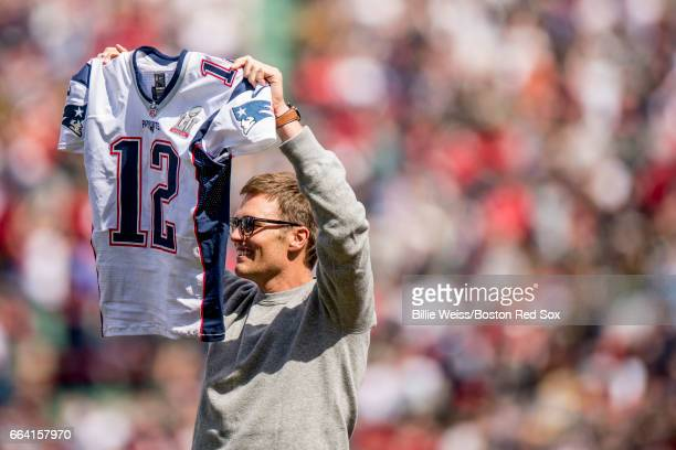 Tom Brady of the New England Patriots displays his jersey during a pregame ceremony before the Boston Red Sox home opener against the Pittsburgh...