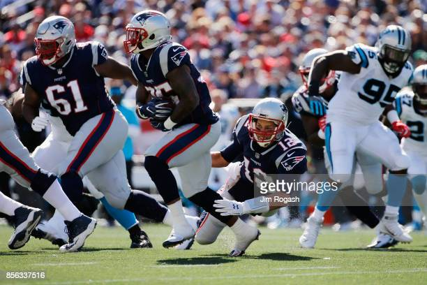 Tom Brady of the New England Patriots falls down after handing off the ball to Mike Gillislee during the first half against the Carolina Panthers at...