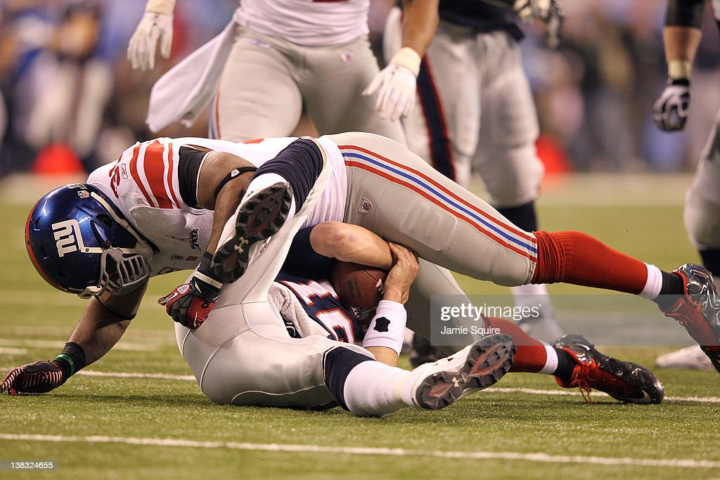 Tom Brady of the New England Patriots gets sacked by Justin Tuck of the New York Giants in the third quarter during Super Bowl XLVI at Lucas Oil...