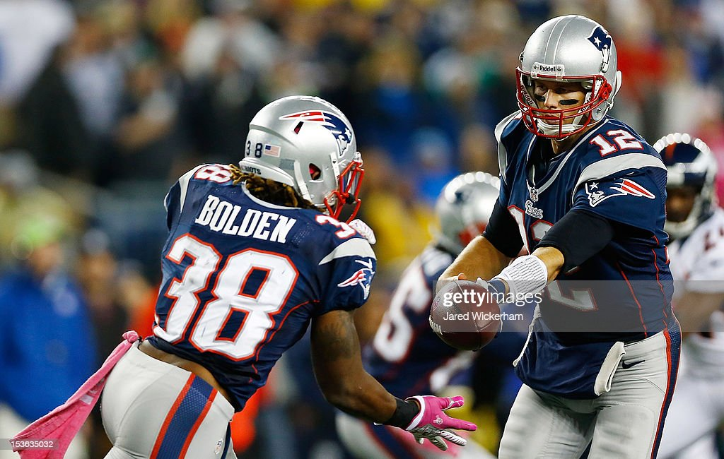 Tom Brady #12 of the New England Patriots hands the ball off to teammate Brandon Bolden #38 against the Denver Broncos during the game on October 7, 2012 at Gillette Stadium in Foxboro, Massachusetts.