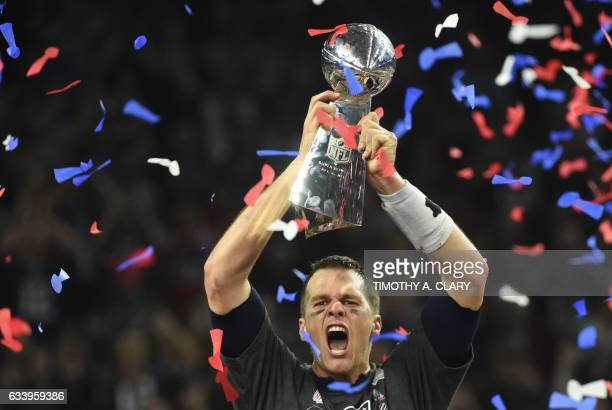 TOPSHOT Tom Brady of the New England Patriots holds the Vince Lombardi Trophy after defeating the Atlanta Falcons 3428 in overtime during Super Bowl...