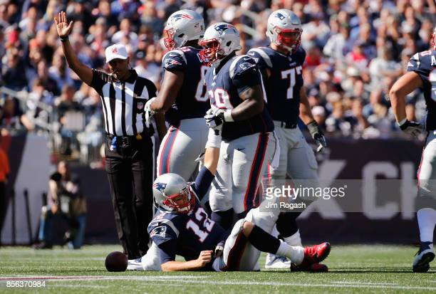 Tom Brady of the New England Patriots is helped up by Shaq Mason after being knocked down during the first half against the Carolina Panthers at...