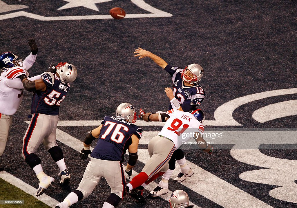 Tom Brady of the New England Patriots is pressured in the endzone by Justin Tuck of the New York Giants in the first quarter resulting in a safety...