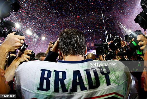 Tom Brady of the New England Patriots is surrounded by the media after defeating the Seattle Seahawks 2824 during Super Bowl XLIX at University of...