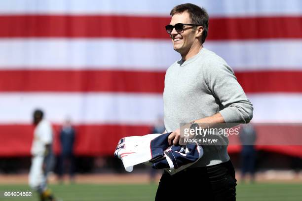 Tom Brady of the New England Patriots looks on after throwing out the first pitch before the opening day game between the Boston Red Sox and the...