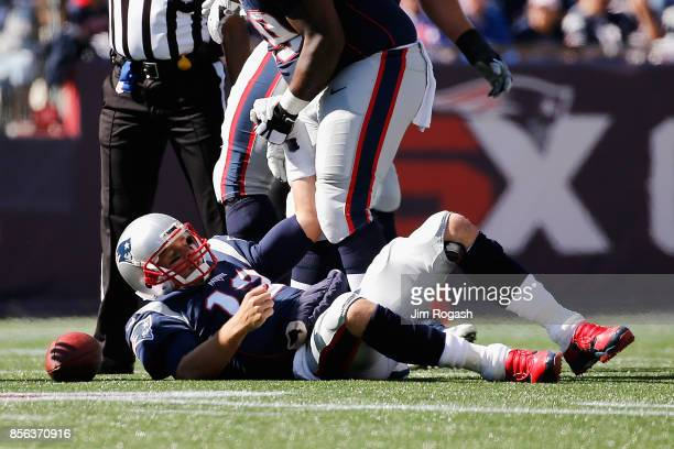 Tom Brady of the New England Patriots reacts after being knocked down during the first half against the Carolina Panthers at Gillette Stadium on...