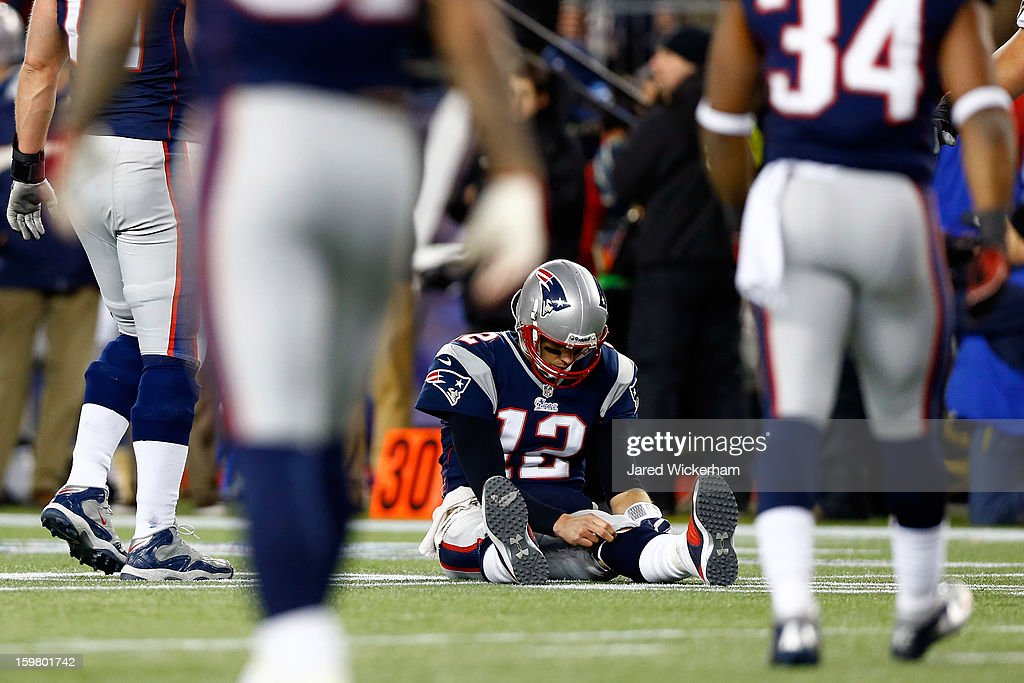 Tom Brady #12 of the New England Patriots sits on the ground after getting knocked down in the fourth quarter against the Baltimore Ravens during the 2013 AFC Championship game at Gillette Stadium on January 20, 2013 in Foxboro, Massachusetts.