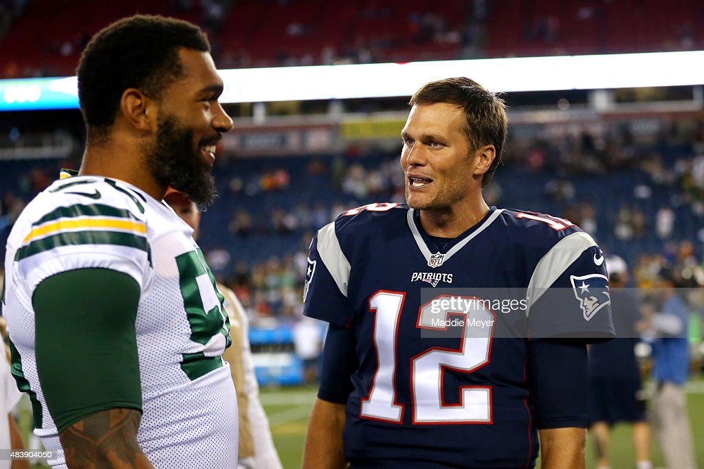 Tom Brady of the New England Patriots speaks turnover Julius Peppers of the Green Bay Packers after a preseason game at Gillette Stadium on August 13...