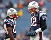 Tom Brady of the New England Patriots talks with teammate Deion Branch on the field prior to their AFC Championship Game against the Baltimore Ravens...