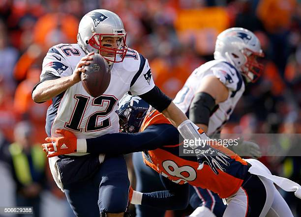 Tom Brady of the New England Patriots tries to evade a tackle by Von Miller of the Denver Broncos in the first half in the AFC Championship game at...