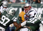 Tom Brady of the New England Patriots tries to shake Sheldon Richardson and Calvin Pace of the New York Jets during their game at MetLife Stadium on...