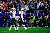 Tom Brady of the New England Patriots walks to the sideline after an interception alongside team mate Sebastian Vollmer of the New England Patriots...