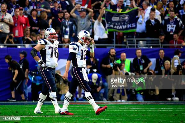 Tom Brady of the New England Patriots walks to the sideline after an interception alongside team mate Sebastian Vollmer of the New England Patriots...