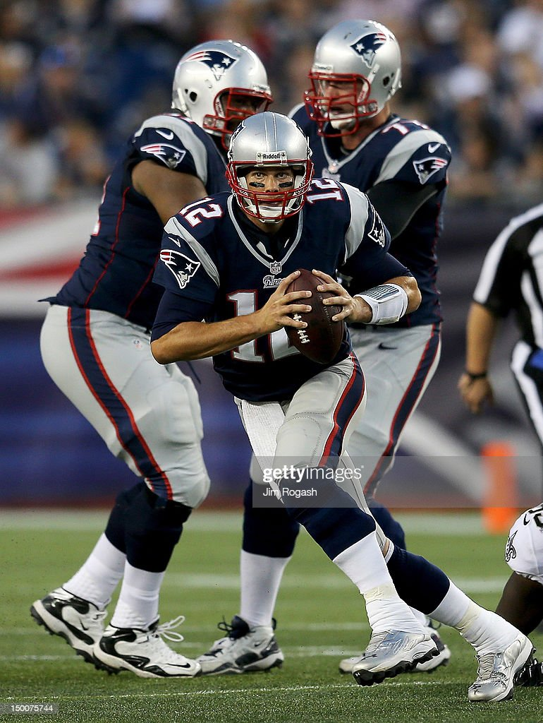 <a gi-track='captionPersonalityLinkClicked' href=/galleries/search?phrase=Tom+Brady+-+American+Football+Quarterback&family=editorial&specificpeople=201737 ng-click='$event.stopPropagation()'>Tom Brady</a> #12 of the New England Patriots works his way out of trouble against the Orleans Saints in the first half at Gillette Stadium on August 9, 2012 in Foxboro, Massachusetts.