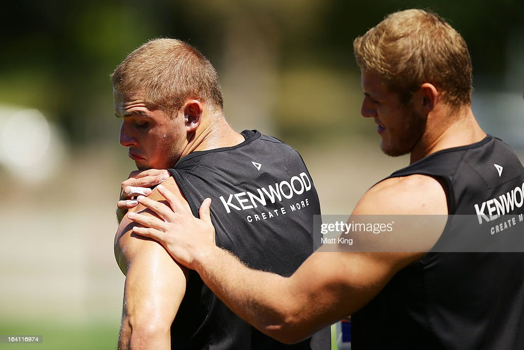 Tom Burgess (R) applies sunscreen to the arm of his twin brother George Burgess (L) during a South Sydney Rabbitohs NRL training session at Redfern Oval on March 20, 2013 in Sydney, Australia.