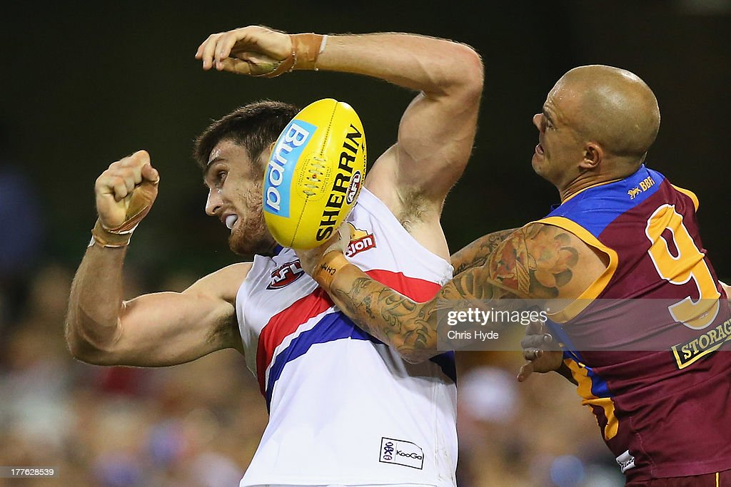 Tom Campbell of the Bulldogs is tackled by <a gi-track='captionPersonalityLinkClicked' href=/galleries/search?phrase=Ashley+McGrath&family=editorial&specificpeople=242768 ng-click='$event.stopPropagation()'>Ashley McGrath</a> of the Lions during the round 22 AFL match between the Brisbane Lions and the Western Bulldogs at The Gabba on August 25, 2013 in Brisbane, Australia.
