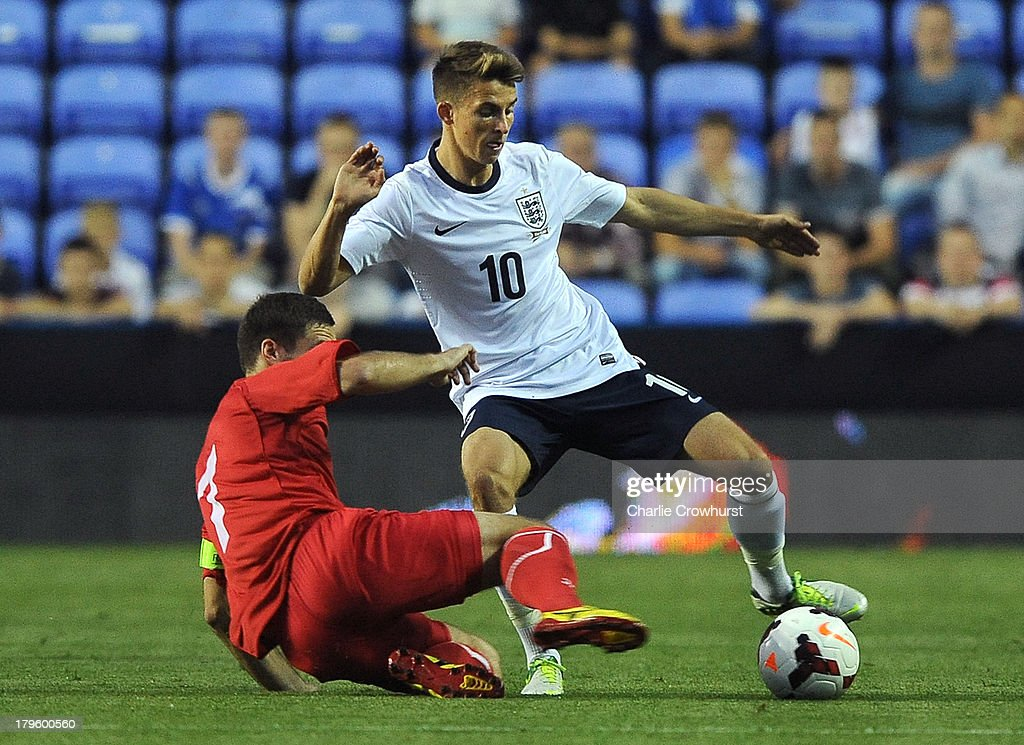 Tom Carroll of England looks to dodge the tackle from Moldova's Eugen Zasaviitchi during the 2015 UEFA European U21 Championships Qualifier between England U21 and Moldova U21 at The Madejski Stadium on September 05, 2013 in Reading, England,