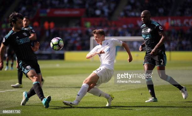 Tom Carroll of Swansea City has his shot blocked by Claudio Yacob of West Bromwich Albion during the Premier League match between Swansea City and...
