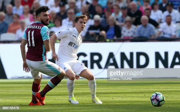 Tom Carroll of Swansea City is challenged by Robert Snodgrass of West Ham United during the Premier League match between West Ham United and Swansea...