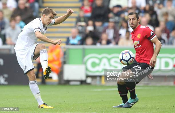Tom Carroll of Swansea City is marked by Henrikh Mkhitaryan of Manchester United during the Premier League match between Swansea City and Manchester...