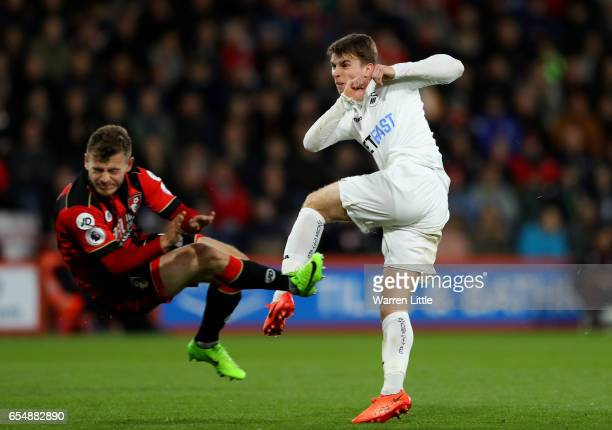 Tom Carroll of Swansea City shoots while Ryan Fraser of AFC Bournemouth attempts to block during the Premier League match between AFC Bournemouth and...