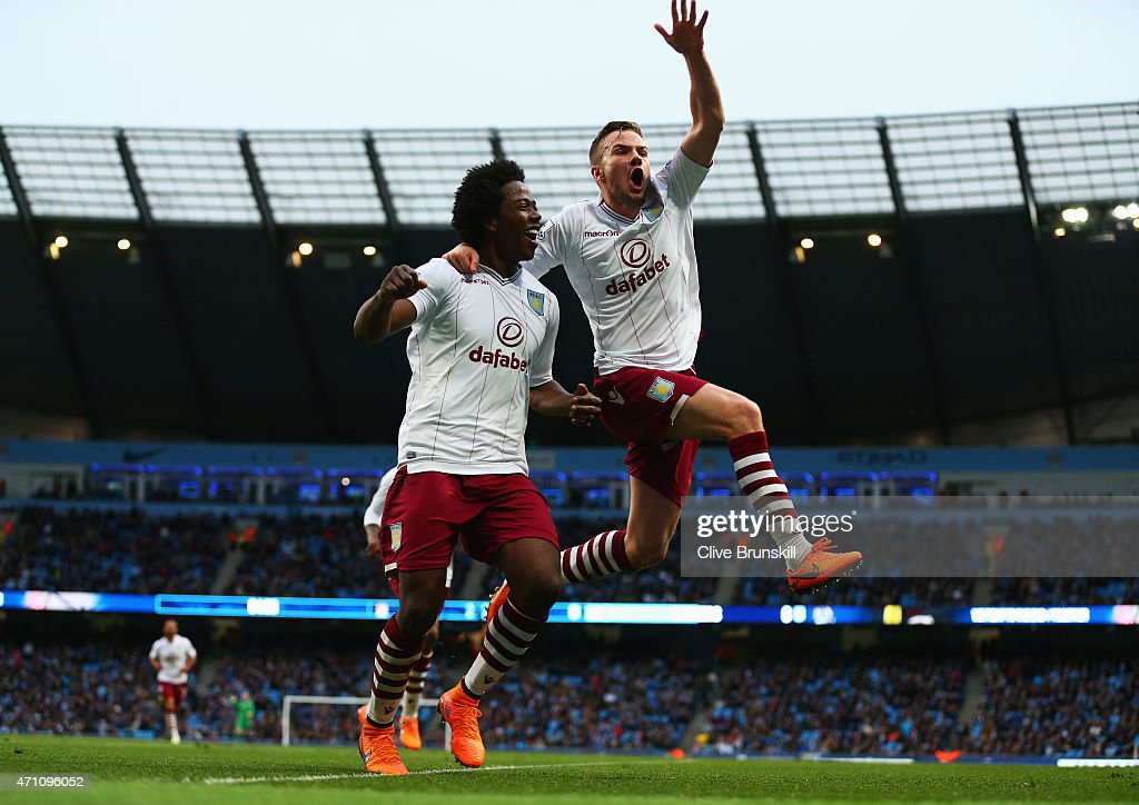 Tom Cleverley of Aston Villa celebrates with goalscorer Carlos Sanchez during the Barclays Premier League match between Manchester City and Aston...