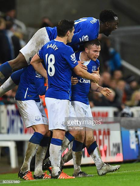 Tom Cleverley of Everton is mobbed by team mates in celebration as he scores their first goal during the Barclays Premier League match between...