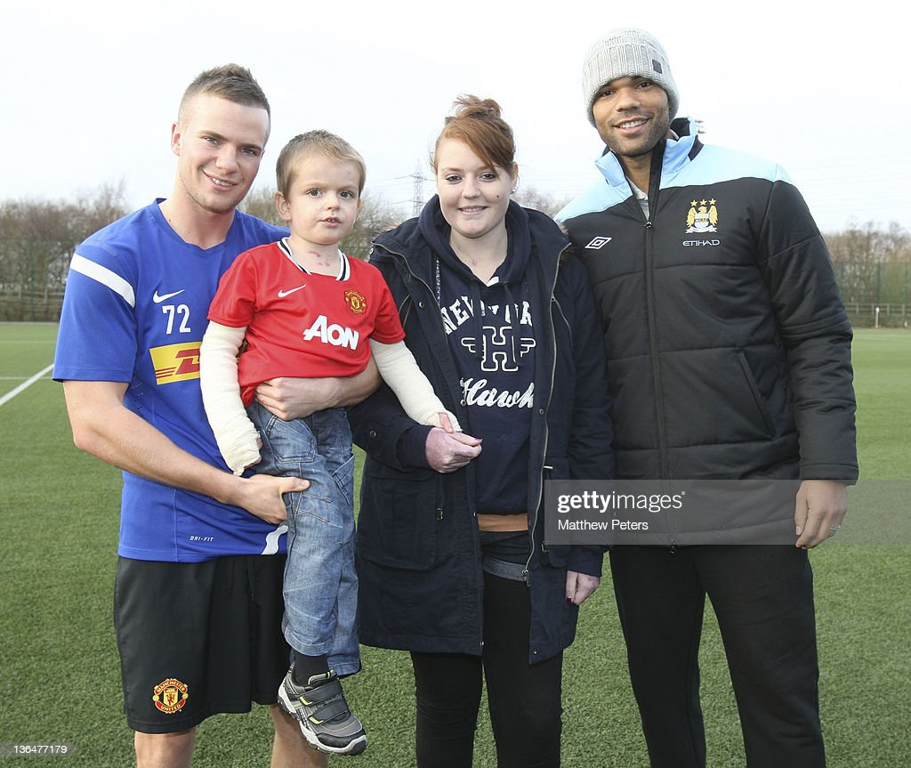 <a gi-track='captionPersonalityLinkClicked' href=/galleries/search?phrase=Tom+Cleverley+-+Soccer+Player&family=editorial&specificpeople=4192565 ng-click='$event.stopPropagation()'>Tom Cleverley</a> (L) of Manchester United and <a gi-track='captionPersonalityLinkClicked' href=/galleries/search?phrase=Joleon+Lescott&family=editorial&specificpeople=687246 ng-click='$event.stopPropagation()'>Joleon Lescott</a> (R) of Manchester City pose with Cailin Van Straaten, 18 and her brother <a gi-track='captionPersonalityLinkClicked' href=/galleries/search?phrase=Zak+Jones&family=editorial&specificpeople=4185625 ng-click='$event.stopPropagation()'>Zak Jones</a>, 4, who were rescued from a house fire in Broadheath in September 2011 at Carrington Training Ground on January 6, 2012 in Manchester, England.
