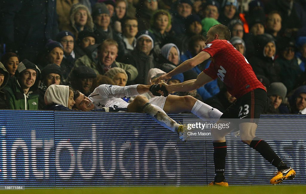 Tom Cleverley of Manchester United helps Gareth Bale of Tottenham Hotspur after he fell over the advertising boards during the Barclays Premier League match between Tottenham Hotspur and Manchester United at White Hart Lane on January 20, 2013 in London, England.