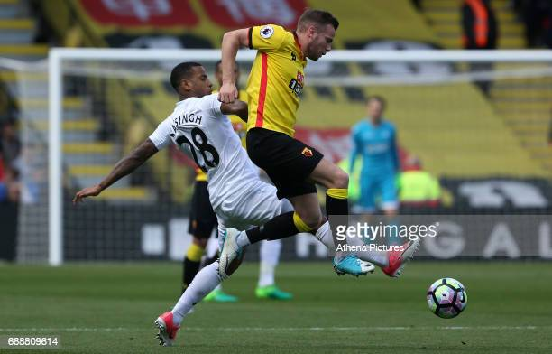 Tom Cleverley of Watford is challenged by Luciano Narsingh of Swansea City during the Premier League match between Watford and Swansea City at...