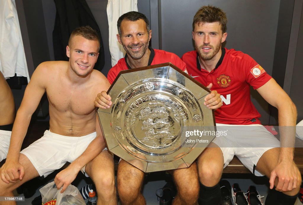 <a gi-track='captionPersonalityLinkClicked' href=/galleries/search?phrase=Tom+Cleverley+-+Soccer+Player&family=editorial&specificpeople=4192565 ng-click='$event.stopPropagation()'>Tom Cleverley</a>, <a gi-track='captionPersonalityLinkClicked' href=/galleries/search?phrase=Ryan+Giggs&family=editorial&specificpeople=201666 ng-click='$event.stopPropagation()'>Ryan Giggs</a> and <a gi-track='captionPersonalityLinkClicked' href=/galleries/search?phrase=Michael+Carrick&family=editorial&specificpeople=214599 ng-click='$event.stopPropagation()'>Michael Carrick</a> of Manchester United pose with the FA Community Shield trophy in the dressing room after the FA Community Shield match between Manchester United and Wigan Athletic at Wembley Stadium on August 11, 2013 in London, England.