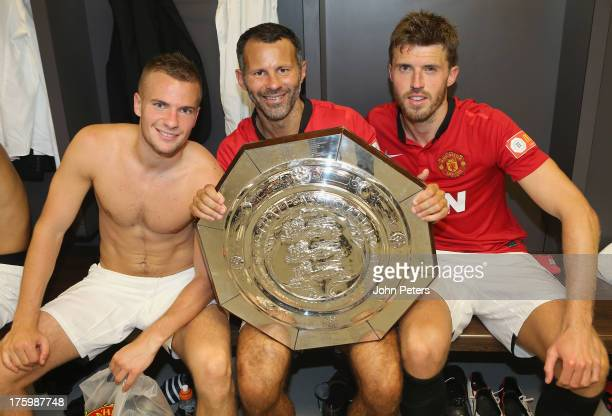 Tom Cleverley Ryan Giggs and Michael Carrick of Manchester United pose with the FA Community Shield trophy in the dressing room after the FA...