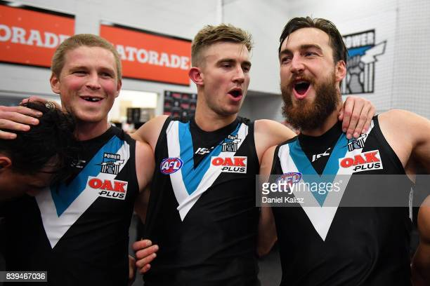 Tom Clurey Dougal Howard and Charlie Dixon of the Power sing the club song after defeating the Suns during the round 23 AFL match between the Port...