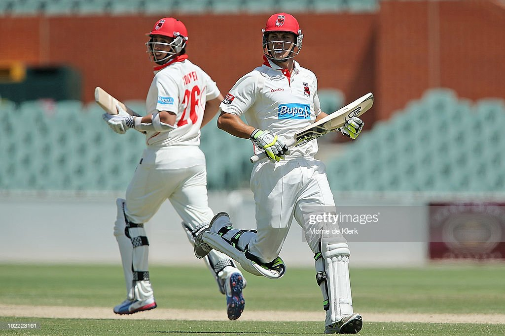 Tom Cooper and Sam Raphael of the Redbacks run between the wickets during day three of the Sheffield Shield match between the South Australian Redbacks and the New South Wales Blues at Adelaide Oval on February 21, 2013 in Adelaide, Australia.