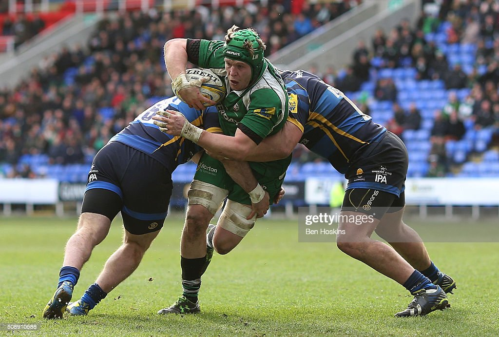 Tom Court of London Irish is tackled by Tevita Cavubati (L) and Matt Cox (R) of Worcester during the Aviva Premiership match between London Irish and Worcester Warriors at Madejski Stadium on February 7, 2016 in Reading, England.