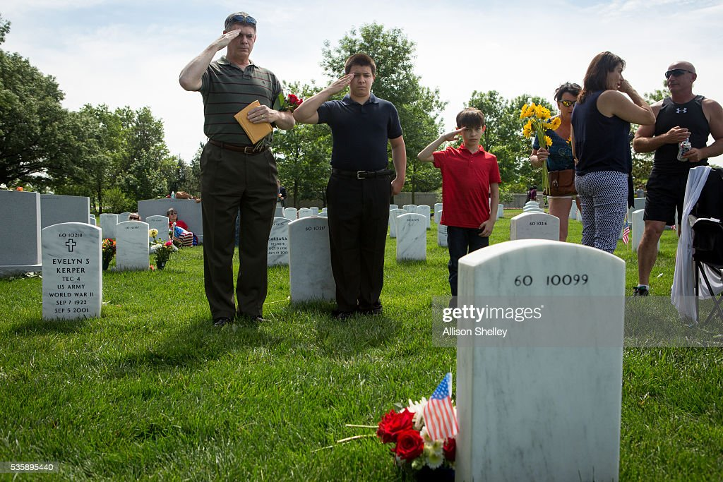 Tom Cowan and his sons Thomas, 17, and Ernest, 11, pay respects at the grave of Gregorio S. Malinag, in Section 60, the burial ground for military personnel killed since 2001, at Arlington National Cemetery on May 30, 2016 in Arlington, Virginia. Cowan, who served in the Air Force for 21 years, has been honoring strangers in this manner for the past 17 years. His oldest son is also buried at the cemetery. 'It's our way of giving something back,' says Cowan, 'and teaching the boys honor and respect.'