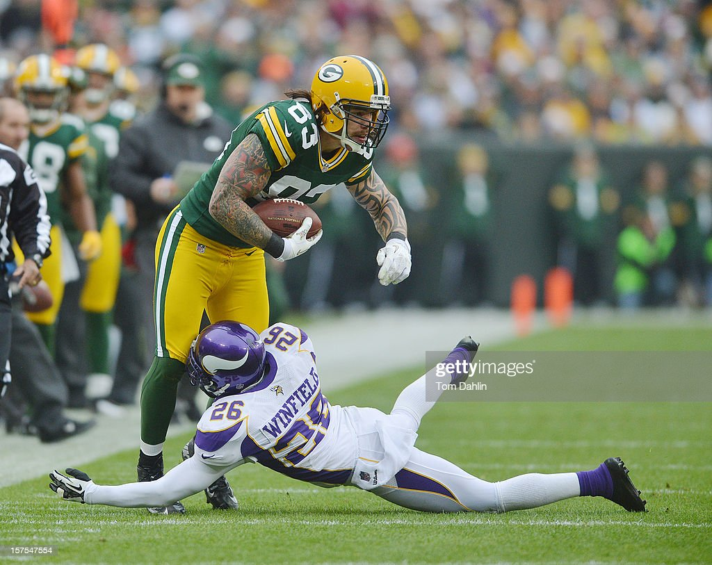 Tom Crabtree #83 of the Green Bay Packers carries the ball against Antoine Winfield #26 of the Minnesota Vikings during an NFL game at Lambeau Field on December 2, 2012 in Green Bay, Wisconsin.