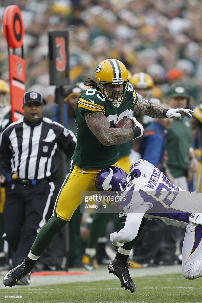 Tom Crabtree #83 of the Green Bay Packers is tackled by Antoine Winfield #26 of the Minnesota Vikings at Lambeau Field on December 2, 2012 in Green Bay, Wisconsin. The Packers defeated the Vikings 23-14.