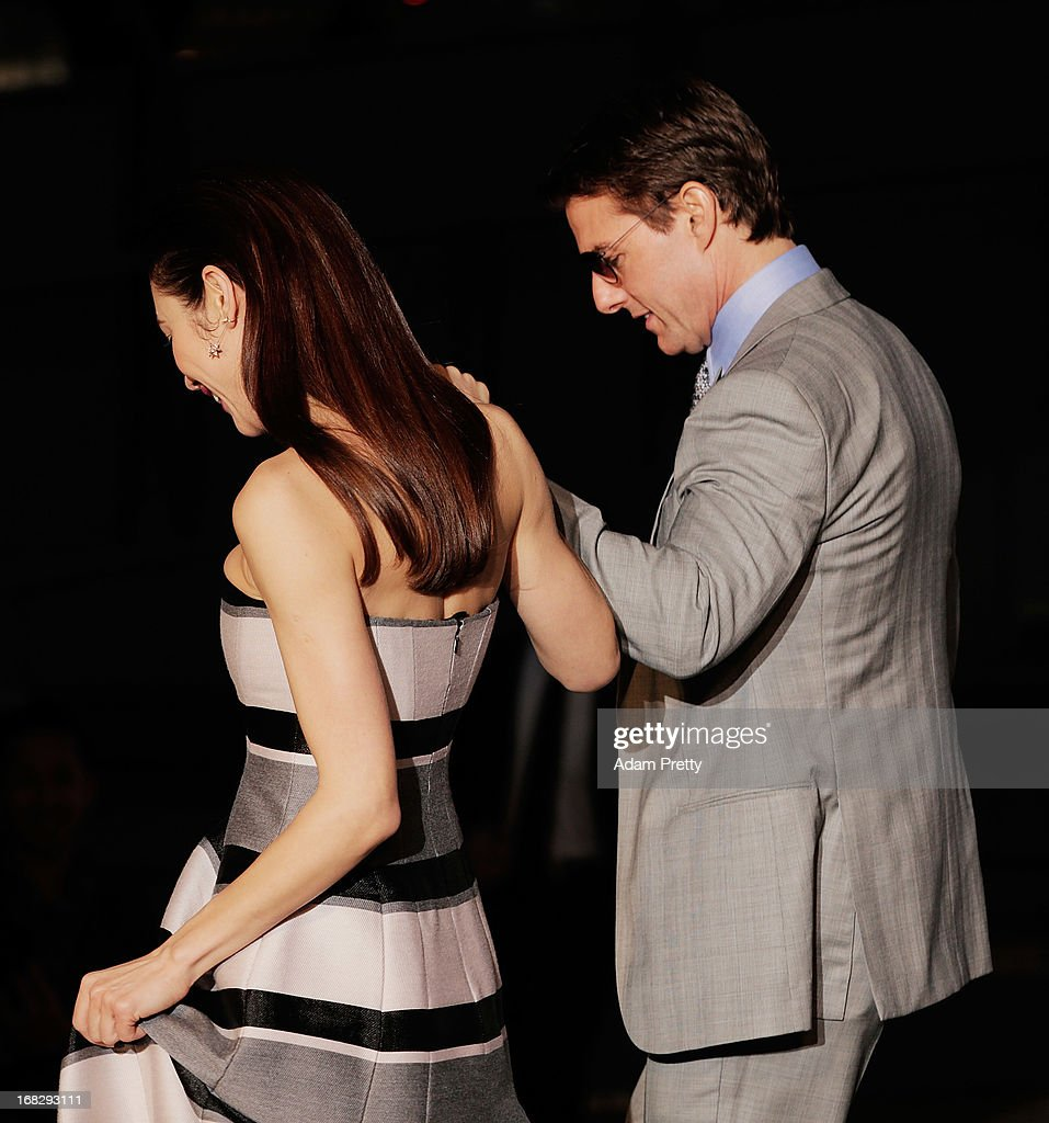 Tom Cruise helps Olga Kurylenko off the stage during the 'Oblivion' Japan Premiere at Roppongi Hills on May 8, 2013 in Tokyo, Japan. The film will open on May 31 in Japan.
