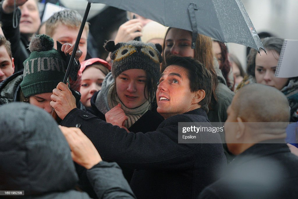 Tom Cruise shelters from the rain as he attends the film premiere of 'Oblivion' at the Oktyabr cinema hall on April 1, 2013 in Moscow, Russia.