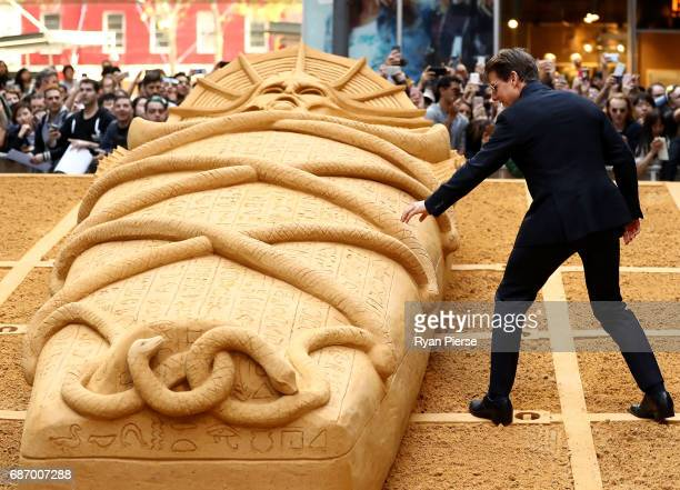 Tom Cruise touches the Mummy sand sculpture during a photo call for The Mummy at World Square on May 23 2017 in Sydney Australia