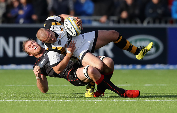 Tom Cruse of Wasps is tackled by Schalk Burger during the Aviva Premiership match between Saracens and Wasps at Allianz Park on October 9 2016 in...