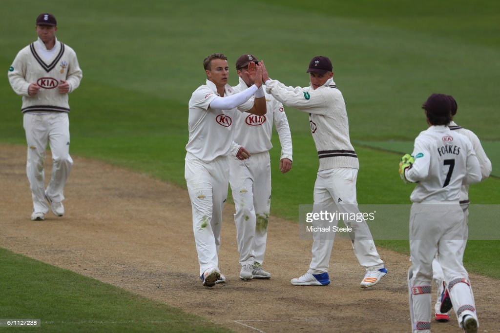 Tom Curran (2L) of Surrey celebrates capturing the wicket of Jonathan Trott of Warwickshire during day one of the Specsavers County Championship Division One match between Warwickshire and Surrey at Edgbaston on April 21, 2017 in Birmingham, England.