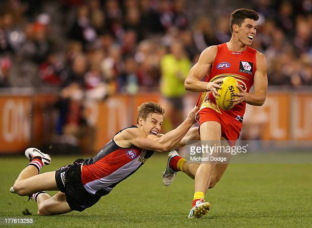 Tom Curren of the Saints tackles Jaeger O'Meara of the Suns during the round 22 AFL match between the St Kilda Saints and the Gold Coast Suns at...
