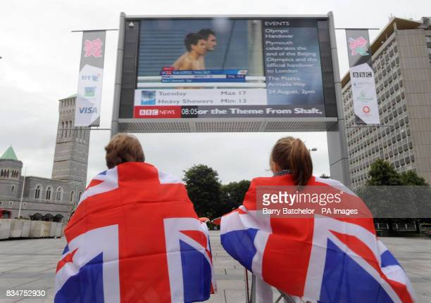 Tom Daley prepares for a dive in the Men's 10m Synchronized Final with partner Blake Aldridge as viewed on the big screen erected in Plymouth city...