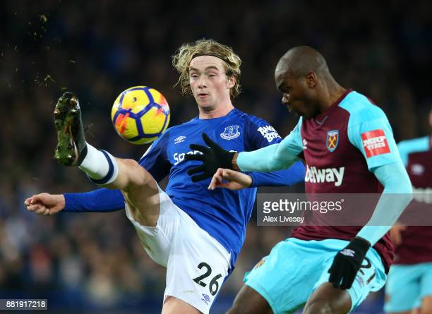 Tom Davies of Everton clears the ball while under pressure from Angelo Ogbonna of West Ham United during the Premier League match between Everton and...