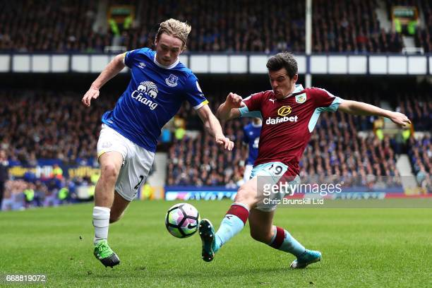 Tom Davies of Everton is challenged by Joey Barton of Burnley during the Premier League match between Everton and Burnley at Goodison Park on April...