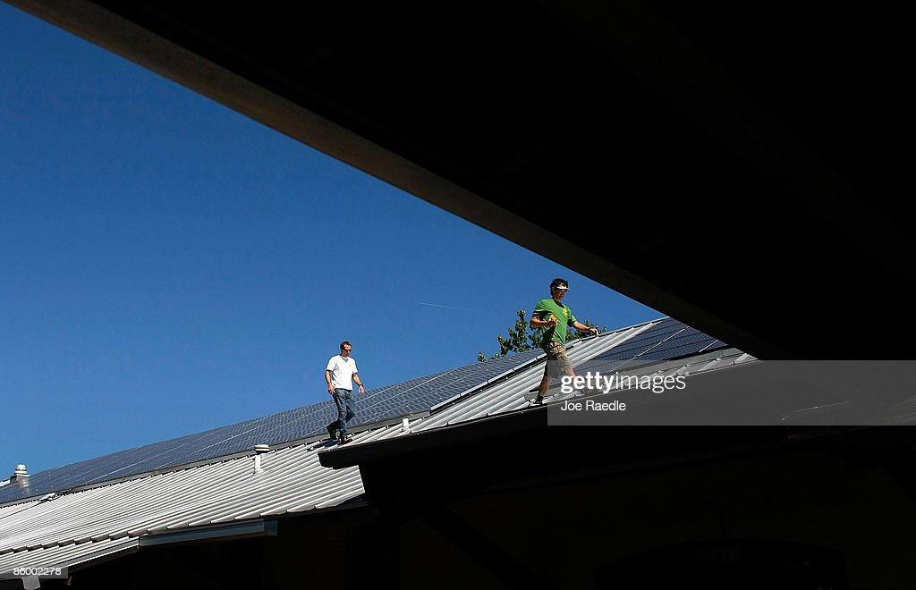 Tom Doughty (L) and Wayne Irwin, who work for Pure Energy Solar, work on the installation of a solar panel system on the roof of a business on April 15, 2009 in Gainesville, Florida. Recently the city of Gainesville through a program initiated by the local Gainesville Regional Utilities became the first city in the nation to have a solar feed-in tariff ordinance which means owners of new solar photovoltaic systems will be eligible to receive 32 cents per kilowatt hour of electricity produced by the system over the next 20 years. The new program has produced a spurt of solar installation projects around the city. Other states and cities around the nation are eyeing the feed-in tariff program as a renewable energy program they might be interested in doing.